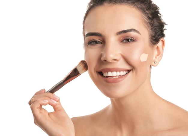 Mooie jonge vrouw met foundation op haar gezicht tegen wit oppervlak