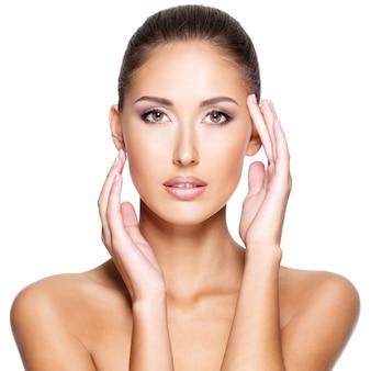 Mooie jonge vrouw met frisse schone huid die haar gezicht met beide handen raakt