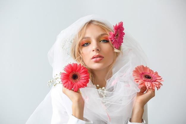 Mooie jonge vrouw met geïsoleerde gerberabloemen