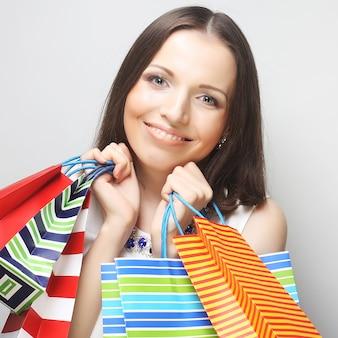 Mooie jonge vrouw met gekleurde boodschappentassen over grijze achtergrond