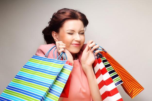Mooie jonge vrouw met gekleurde boodschappentassen