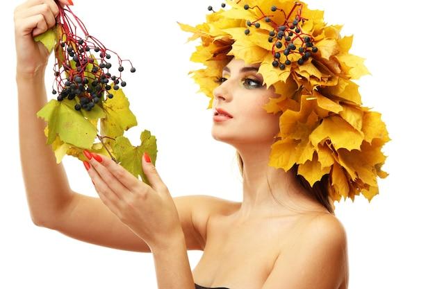 Mooie jonge vrouw met gele de herfstkroon, op wit