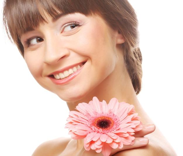 Mooie jonge vrouw met gerberbloem die op wit wordt geïsoleerd