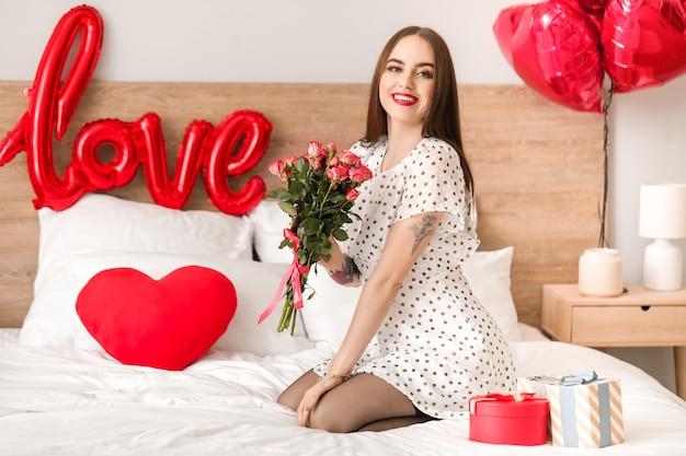 Mooie jonge vrouw met geschenken en bloemen in de slaapkamer. valentijnsdag viering