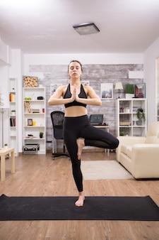 Mooie jonge vrouw met gesloten ogen het beoefenen van boom yoga pose staande in één been.