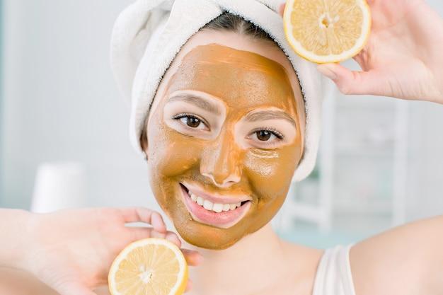 Mooie jonge vrouw met gezichts moddermasker en de helft van citroen op lichte ruimte in kuuroordcentrum