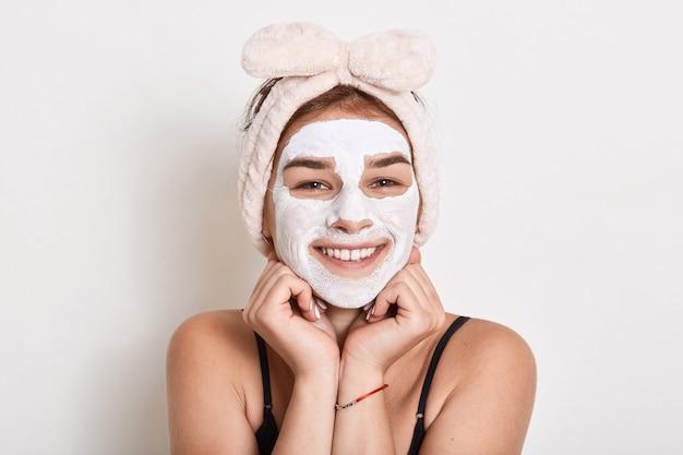 Mooie jonge vrouw met gezichtsmasker op haar gezicht, huidverzorging en behandelingsprocedures, natuurlijke schoonheid en cosmetologie, glimlachend meisje houdt vuisten onder de kin.