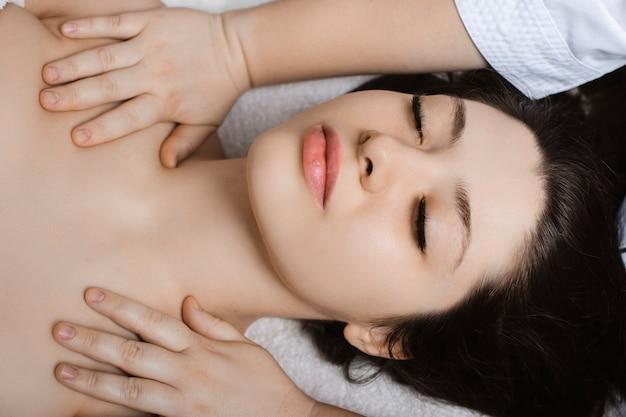 Mooie jonge vrouw met gezichtsmassage terwijl ze in een wellness-spa.