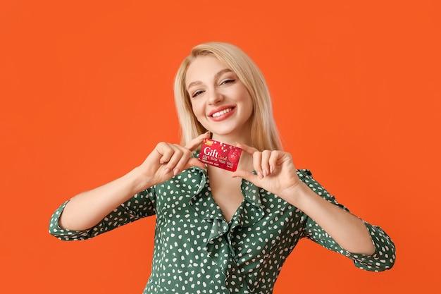 Mooie jonge vrouw met gift card op kleur oppervlak
