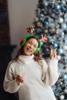 Mooie jonge vrouw met glas champagne thuis