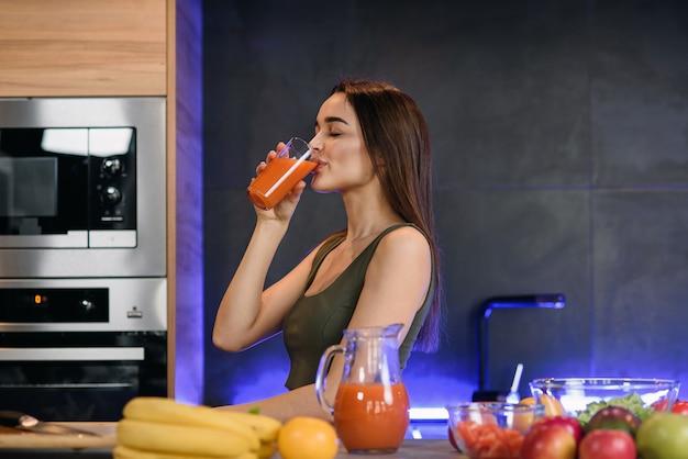 Mooie jonge vrouw met glas jus d'orangezitting bij keukenlijst