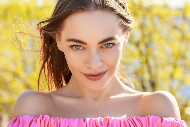 Mooie jonge vrouw met goed verzorgde gezichtshuid in een roze jurk