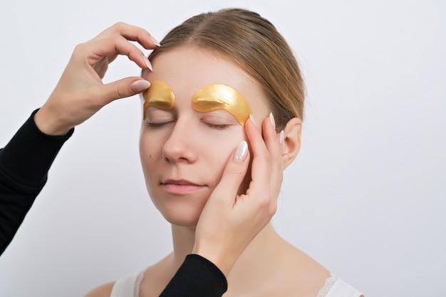 Mooie jonge vrouw met gouden hydrogel flarden op haar gezicht, geïsoleerd op wit. huidverzorging concept.