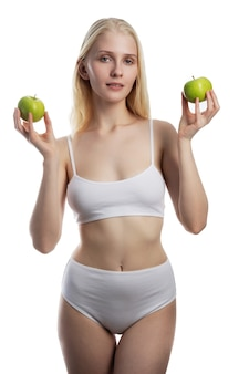 Mooie jonge vrouw met groene appel close-up op witte muur