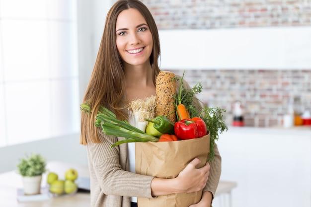 Mooie jonge vrouw met groenten in boodschappentas thuis.