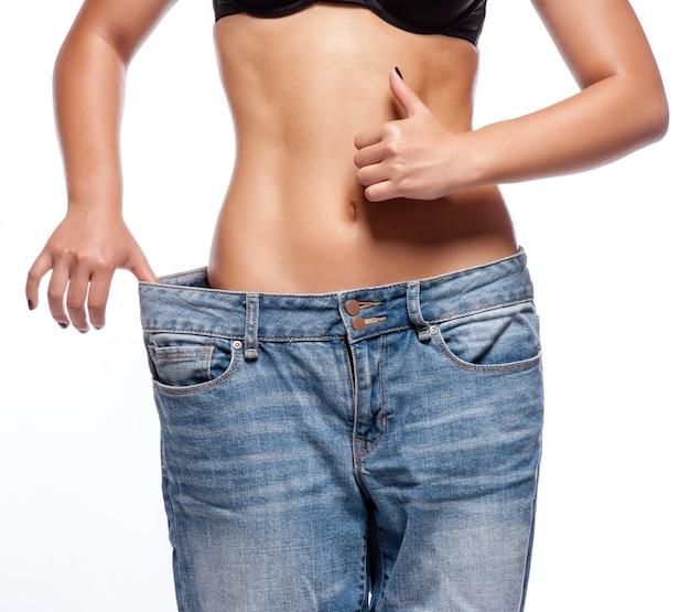 Mooie jonge vrouw met grote jeans, die op wit wordt geïsoleerd
