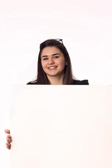 Mooie jonge vrouw met grote lege poster op de witte muur
