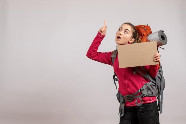 Mooie jonge vrouw met grote rugzak die karton omhoog houdt