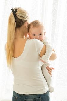 Mooie jonge vrouw met haar 3 maanden oude babyjongen bij groot raam