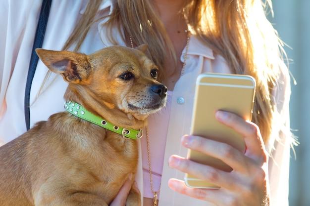 Mooie jonge vrouw met haar hond met behulp van mobiele telefoon.