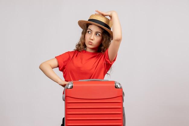 Mooie jonge vrouw met haar valise staande op wit