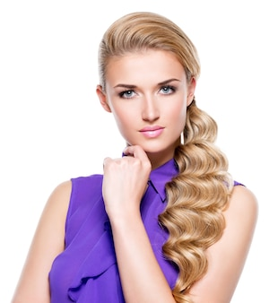 Mooie jonge vrouw met hand dichtbij gezicht. mannequin met lang blond krullend haar. geïsoleerd op een witte muur.