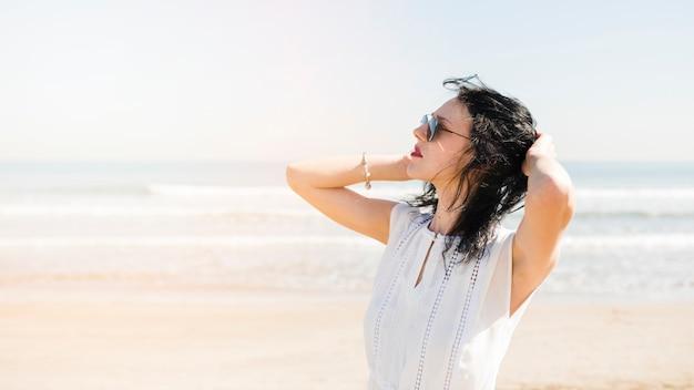 Mooie jonge vrouw met hand op haar hoofd staande in de buurt van de zee op het strand