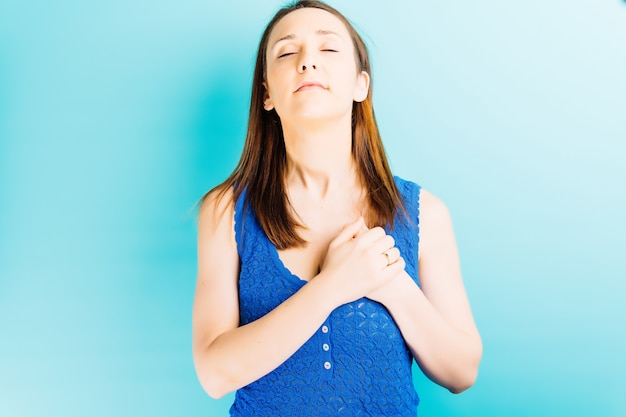 Mooie jonge vrouw met handen op het hart en gesloten ogen met blauwe achtergrond en copyspace