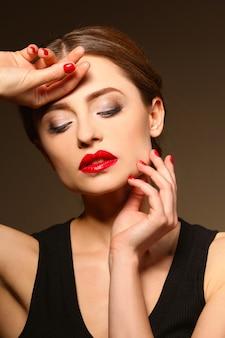 Mooie jonge vrouw met heldere lippen op donkere muur, close-up