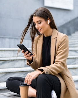 Mooie jonge vrouw met herfstjas zittend op een bankje, afhaalkoffie drinken, mobiele telefoon gebruiken