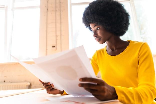 Mooie jonge vrouw met het afro-kapsel die op kantoor werkt
