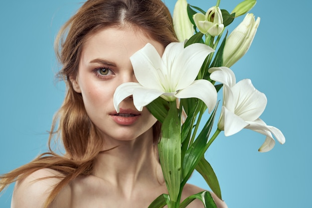 Mooie jonge vrouw met het witte leliebloem stellen op een blauwe muur, romantisch teder beeld