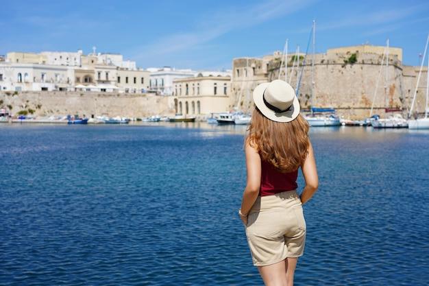 Mooie jonge vrouw met hoed kijkend naar het historische dorp gallipoli in salento, italië