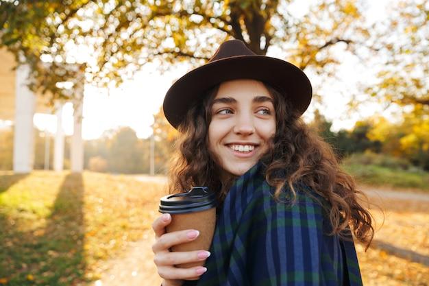Mooie jonge vrouw met hoed wandelen in het park in de herfst, kopje afhaalmaaltijden koffie te houden