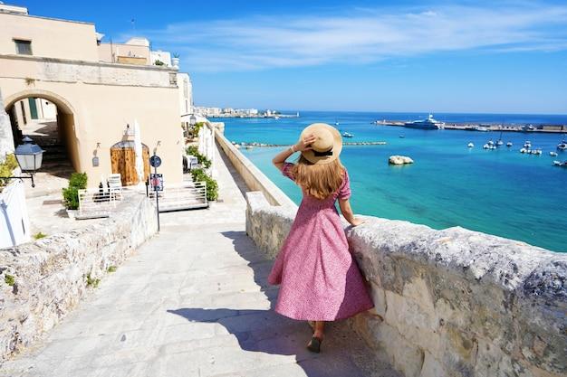 Mooie jonge vrouw met hoed wandelen langs de oude muren van otranto en kijken naar een prachtig panoramisch uitzicht op het dorp otranto in salento, italië