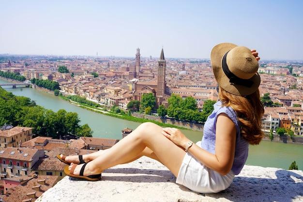 Mooie jonge vrouw met hoed zittend op de muur en kijkt naar een prachtig panoramisch uitzicht over de stad verona met de rivier de adige, italië