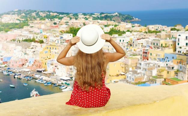 Mooie jonge vrouw met hoed zittend op de muur kijken naar een prachtig panoramisch uitzicht op procida island, napels, italië.