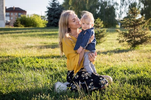Mooie jonge vrouw met jongen op de madeliefjeweide op een zonnige dag. gelukkige familie op zomerzonsondergang. mama met baby. Premium Foto