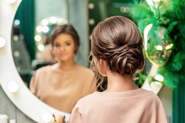 Mooie jonge vrouw met kapsel in de spiegel kijken in de schoonheidssalon.