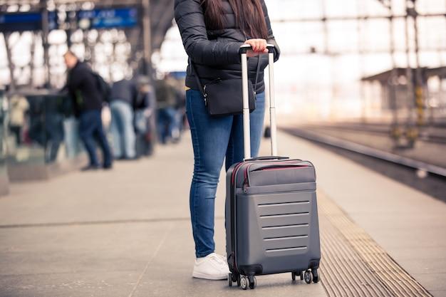 Mooie jonge vrouw met kleine handbagage wachten op het treinstation voor haar trein, transport concept