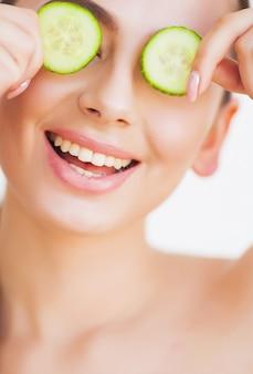 Mooie jonge vrouw met komkommers op ogen.