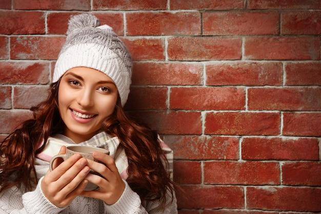Mooie jonge vrouw met kop warme koffie staande in de buurt van bakstenen muur
