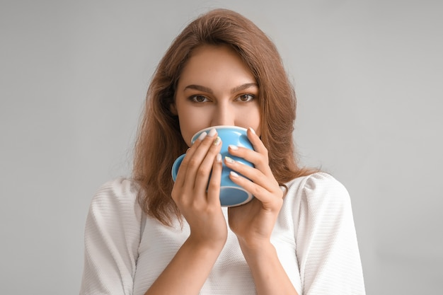 Mooie jonge vrouw met kopje thee op grijs