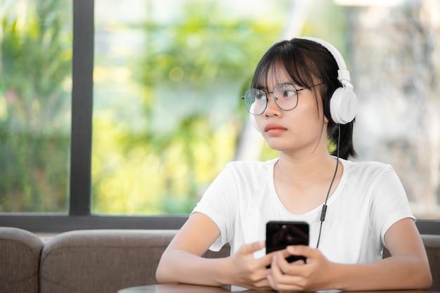 Mooie jonge vrouw met koptelefoon ontspannen op kamer, ze luistert naar muziek met behulp van een smartphone, chill out en vrije tijd concept