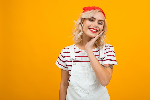 Mooie jonge vrouw met kort blond krullend haar en lichte make-up in witte overall en rode hoed gesticuleerd en glimlacht, portret geïsoleerd op oranje