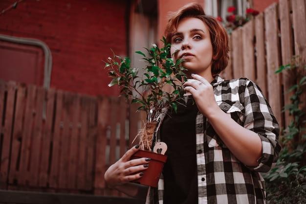 Mooie jonge vrouw met kort rood haar in een geruite overhemd met een bloem in een pot in de achtertuin