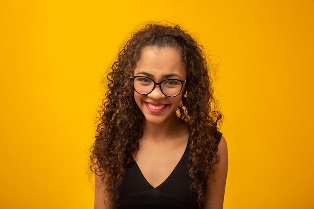 Mooie jonge vrouw met krullend haar blij met haar bril.
