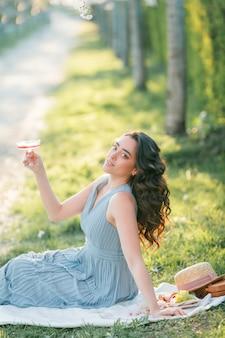 Mooie jonge vrouw met krullend haar drinkt roze champagne in de bloeiende sakuratuin. picknick in de natuur. voorjaar.