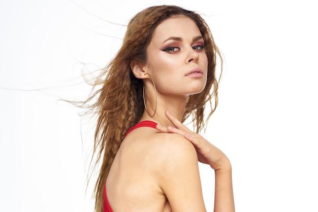 Mooie jonge vrouw met krullend haar in een rood zwempak tropisch beeld