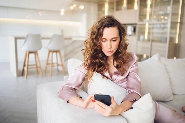 Mooie jonge vrouw met krullend haar in roze pyjama's op witte bank in de ochtend. dame die smartphone in de woonkamerbinnenland van de skandinavische stijl gebruiken.